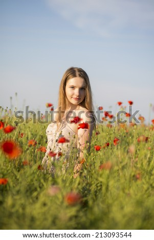 Woman at white dress posing on poppy field - stock photo