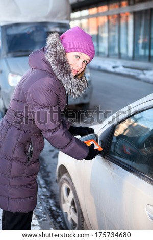 Woman at winter cleaning car windows and mirrors before the trip - stock photo