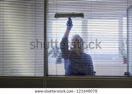 Woman at work, professional female cleaner cleaning and wiping window in office with detergent - stock photo