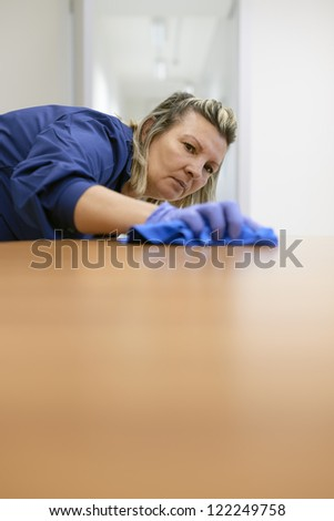 Woman at work, professional maid cleaning desk in office. Copy space