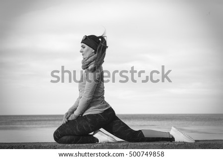 Woman athlete girl training wearing warm sporty clothes outside by seaside in cold weather. Sports and activities in winter or autumn time.