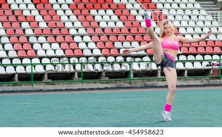 Woman athlete on the stadium. Fitness-woman make exercises.