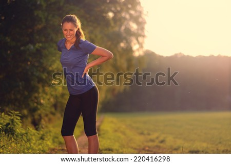 Woman athlete pausing to relieve her back pain holding her hand to her lower back with a grimace while out training in the countryside with copy space - stock photo