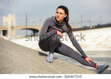 Woman athlete runner stretching her legs in city urban environment exercise gear and sneakers - stock photo
