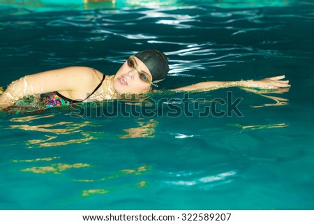 Woman athlete swimming performing crawl style stroke in pool. Active human swimmer taking breath. Water sport comptetition.