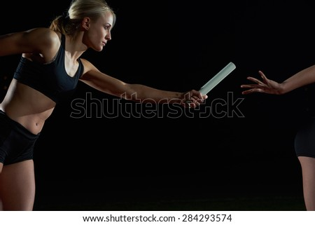 woman athletic runners passing baton in relay race - stock photo