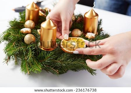 Woman attaches orange on Christmas wreath on a white table - stock photo