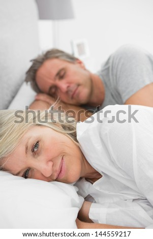 Woman awake as her partner is sleeping in bed at home in bedroom