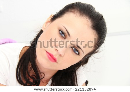 Woman awaken by an alarmclock in her bedroom - stock photo