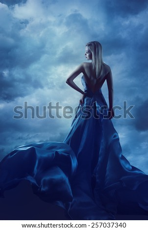 Woman Back Portrait in Evening Dress, Lady in Silk Gown, Cloth Flying over Blue Sky, Night Clouds - stock photo