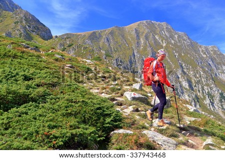Woman backpacker descending a steep mountain trail - stock photo