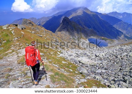 Woman backpacker descending towards distant lake with mountains in the background - stock photo