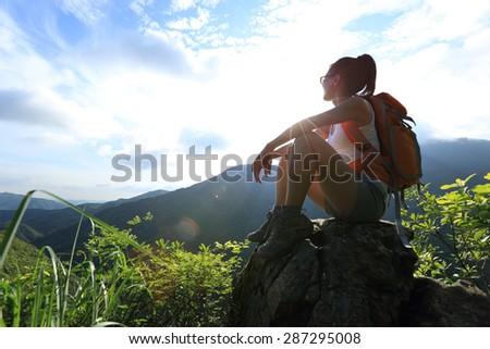 woman backpacker on mountain peak enjoy the view  - stock photo