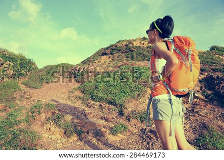 woman backpacker on mountain trail enjoy the view