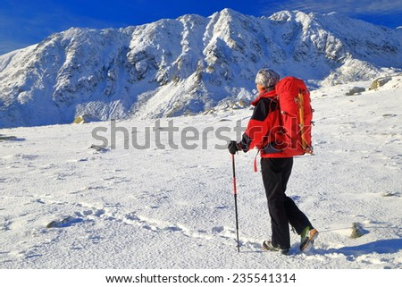 Woman backpacker on snowy trail surrounded by mountains - stock photo