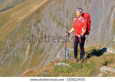 Woman backpacker standing with mountains in the background - stock photo