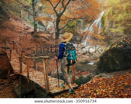 Woman backpacker walking on a wooden bridge over a river in the beautiful autumn forest. Hiking in the autumn forest trees.