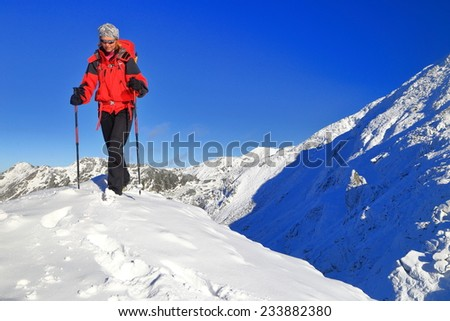 Woman backpacker walking on top of snow covered mountain