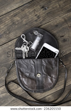 woman bag stuff, handbag over rustic wooden background - stock photo