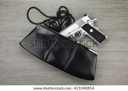 Woman bag with gun hidden, Handgun and accessories falling from a woman's purse. - stock photo