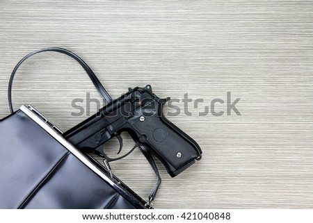 Woman bag with gun hidden, Handgun falling from a woman's purse. - stock photo