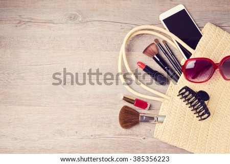 Woman bag with makeup and fashion objects. View from above