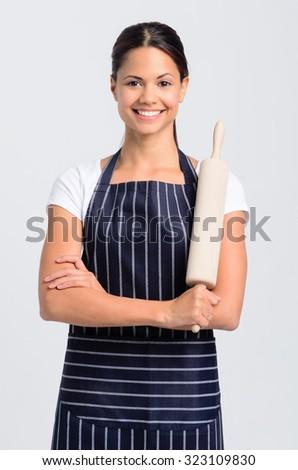 Woman baker holding a rolling pin, isolated on grey background