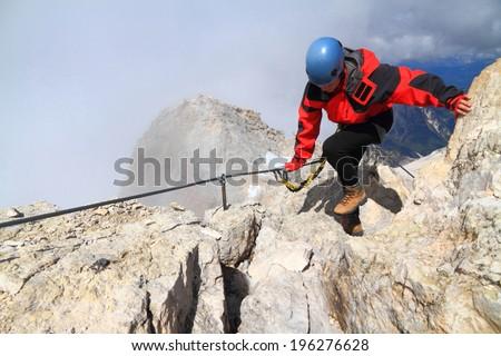 Woman balances on sunny ridge along via ferrata cable, Dolomite Alps, Italy - stock photo
