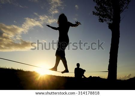 woman balancing in slack line , slacklining , and man looks at him  at sunset    - stock photo