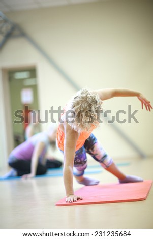 Woman balancing on one hand and legs in the gym, fitness exercises concept