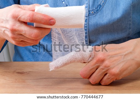 Woman bandage yourself wounding finger