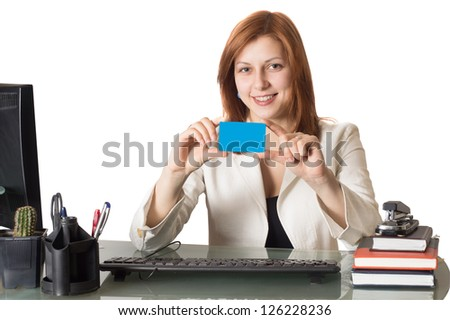 Woman banker holds a credit card in hand sitting at a desk in an office on a white background isolated