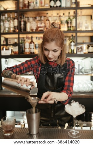 Woman bartender pouring alcohol cocktail in wineglass from shaker