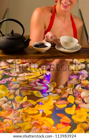 Woman bathing in spa with color therapy, the bathtub is lit with colorful lights, lots of flower petals on tub and tea - stock photo