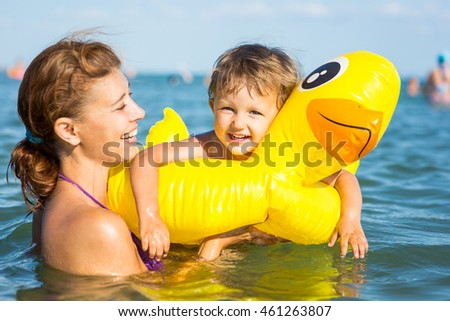 Woman bathing in the sea with a baby