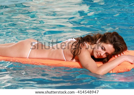 Woman bathing on inflatable mattress in the pool