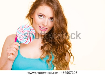 Woman beautiful cheerful girl holding colorful lollipop candy in hand having fun. Sweet food and happiness concept. Studio shot on bright background