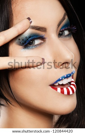 Woman beautiful face with perfect makeup on black background. on the lips and eyes painted an American flag - stock photo