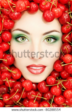 woman beautiful face with red ripe big fresh cherry - stock photo