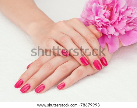 Woman beautiful hands with manicure and pink peony flower - stock photo