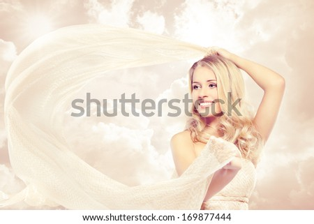 Woman beautiful happy blonde carefree smiling with flying fabric over sky background - stock photo
