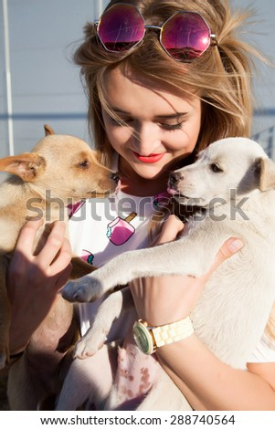 woman beautiful young happy with long blonde hair in summer shirt holding small dog  and playing.young girl playing with stray animals on the street, a girl holding a beautiful puppies  - stock photo