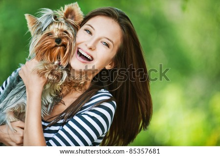 woman beautiful young happy with long dark hair in striped sweater holding small dog