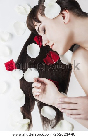 Woman Beauty Concept: Portrait of Young Caucasian Woman With Soft Silk Skin and Dark Long Hair. Rose Leafs are used. Vertical Image Composition - stock photo