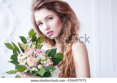 Woman beauty concept. Young beautiful woman with long curly hair and bouquet of flowers.