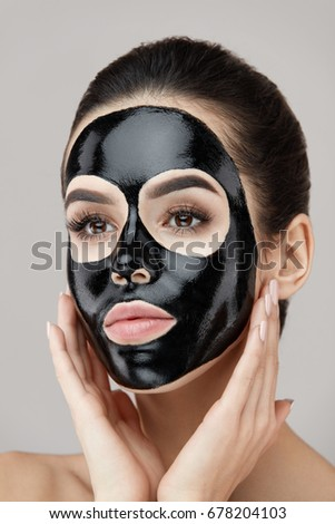 Woman Beauty Face Skin Mask. Closeup Of Attractive Girl Applying Black Smooth Peeling Mask On Facial Skin. Portrait Of Beautiful Female With Natural Makeup And  Cosmetic Peel Off Mask. High Resolution