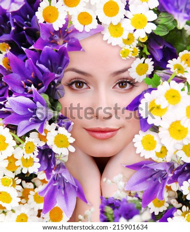 Woman beauty face with beautiful flowers frame, close-up - stock photo