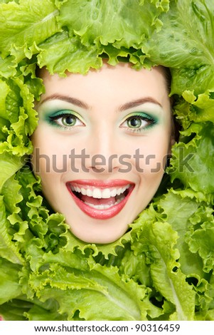 woman beauty face with green fresh lettuce leaves frame - stock photo