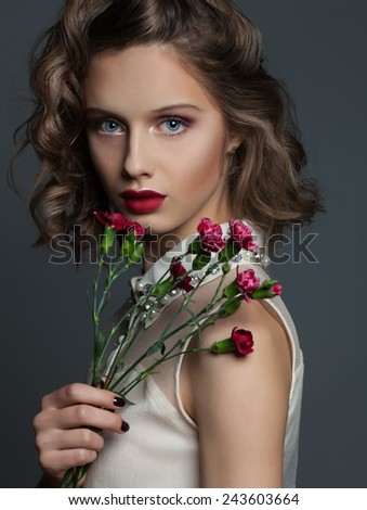 Woman beauty. Portrait ot young gorgeous glamour woman with blue eyes, red lips, flowers over grey background. Perfect make up and hair style. Close up. - stock photo
