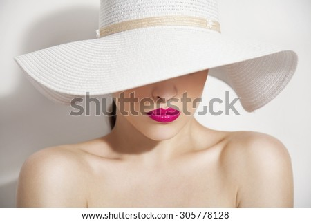 woman beauty portrait with pink lips and summer white hat, studio - stock photo